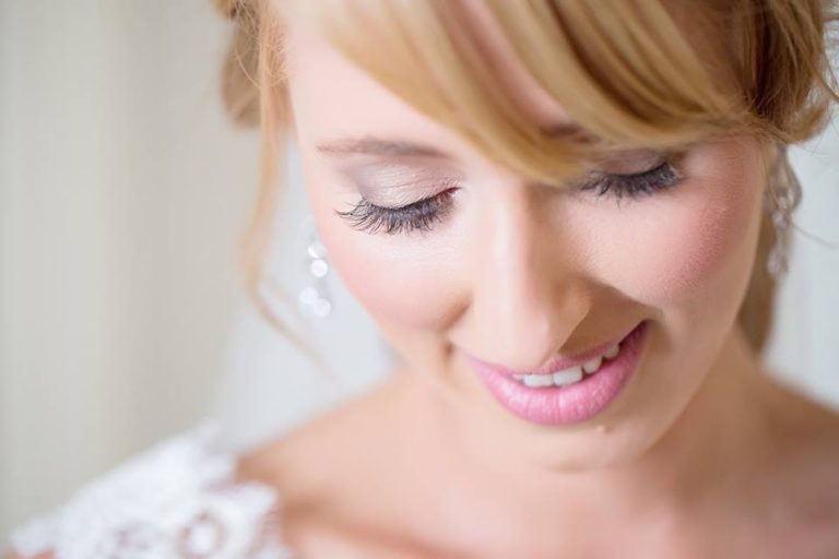 Red head bride looking down with pink lipstick and individual lashes