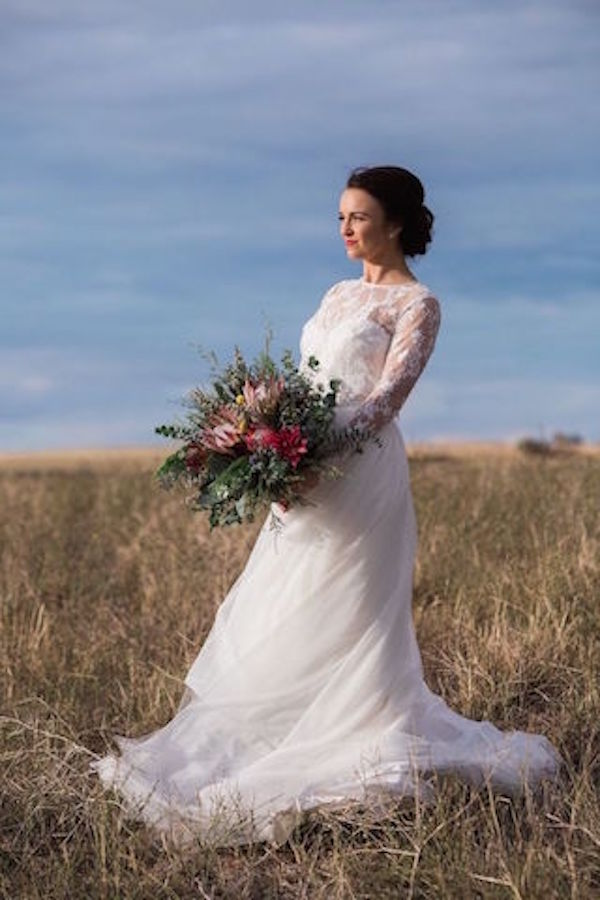 Vintage bride in Lameroo in lace wedding dress with vintage hairstyle and wild flowers