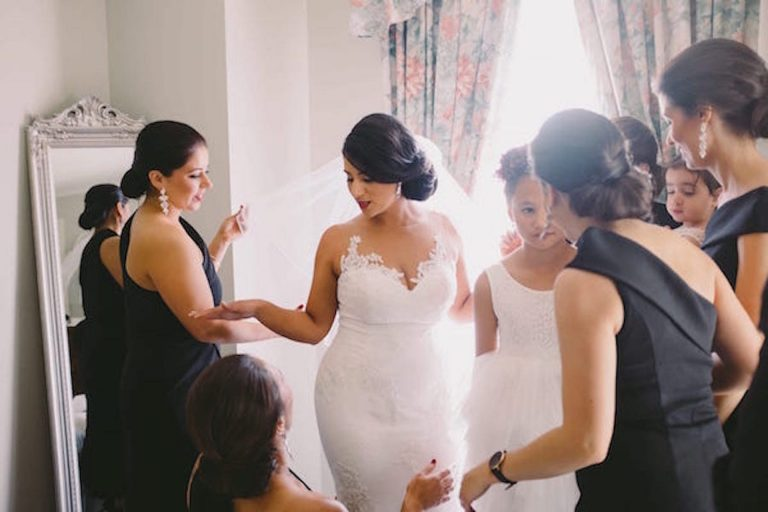 Greek brunette bride in wedding dress surrounded by bridesmaids