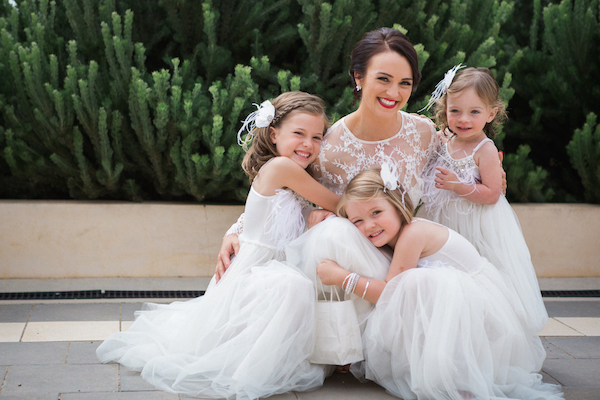 Bride wearing red lipstick kneeling down with flower girls for a wedding photo