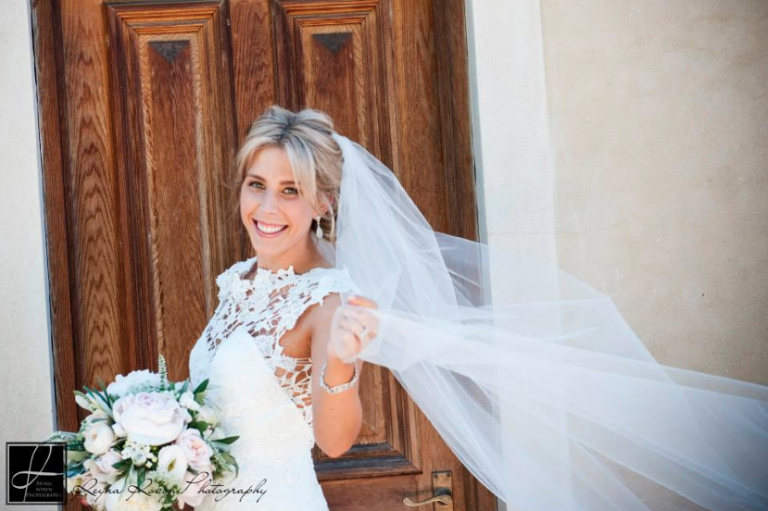 Blonde bride with natural makeup in Adelaide with veil blowing in wind