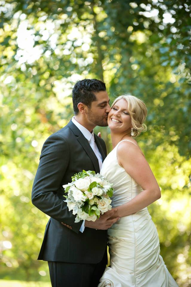 Blonde bride receiving a kiss from groom under trees at Glen Ewin Estate