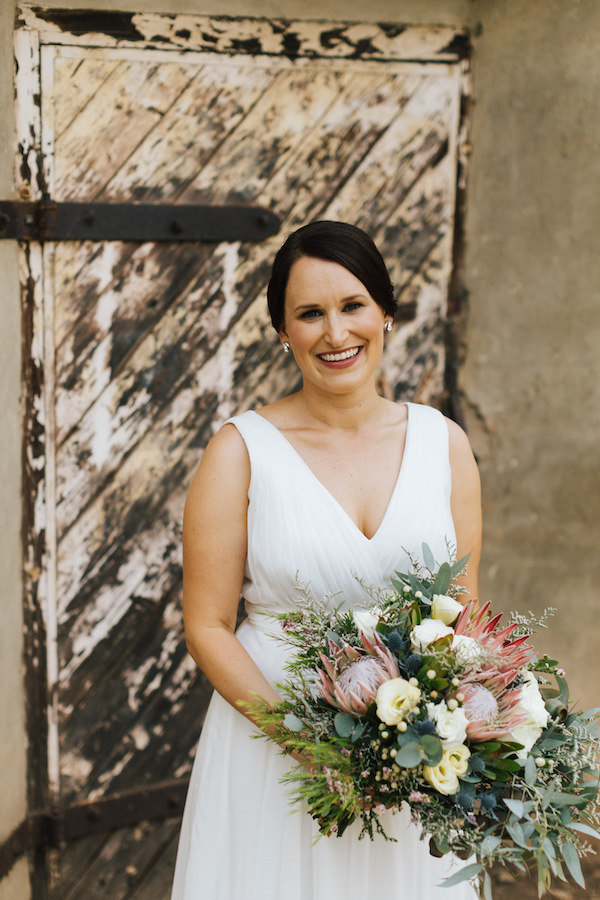 Smiling bride looking at camera with rustic background wearing dark lipstick and natural makeup