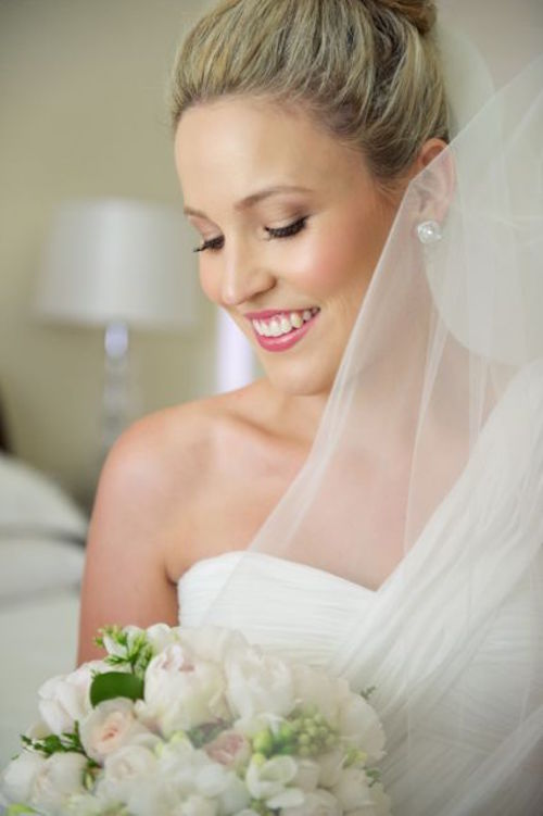 New bride looking down towards wedding bouquet with dewy makeup and pink lipstick