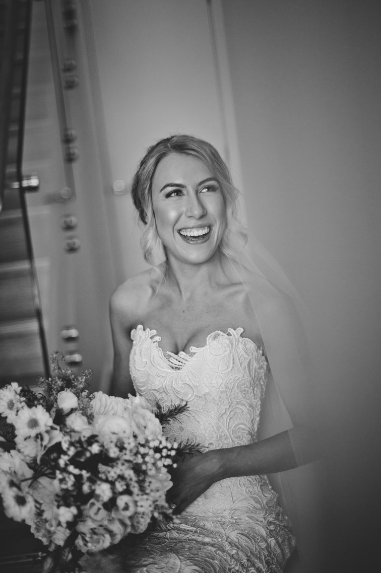 Black and white photograph of bride laughing with makeup glow