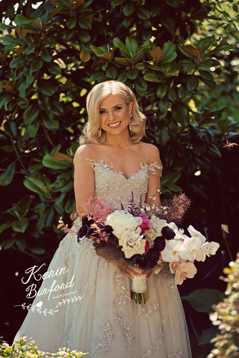 Blonde bride with water waves in silver dress holding wild flowers
